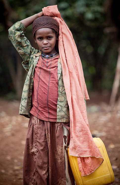 Girl carrying yellow jerry can for water in Bale Mountains, Ethiopia