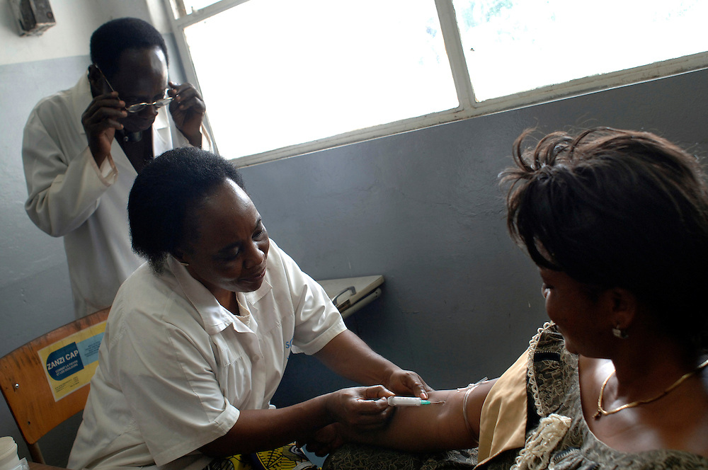 Kinshasa November 30, 2005 - Kinshasa General Hospital, doctor taking a blood sample from the arm of a  woman - The Kinshasa General Hospital, is far from being a bush dispensary. With its 2,000 beds and its 2,250 employees (doctors, nurses and administrative personnel), it is one of Africa's most impressive medical facilities. It offers a full range of services and is the undisputed referral centre for the Congolese capital. Its patients the sick, accident victims and war casualties, both civilian and military  have one thing in common: their suffering, which the staff do their best to alleviate with the means available. But those means are often woefully inadequate