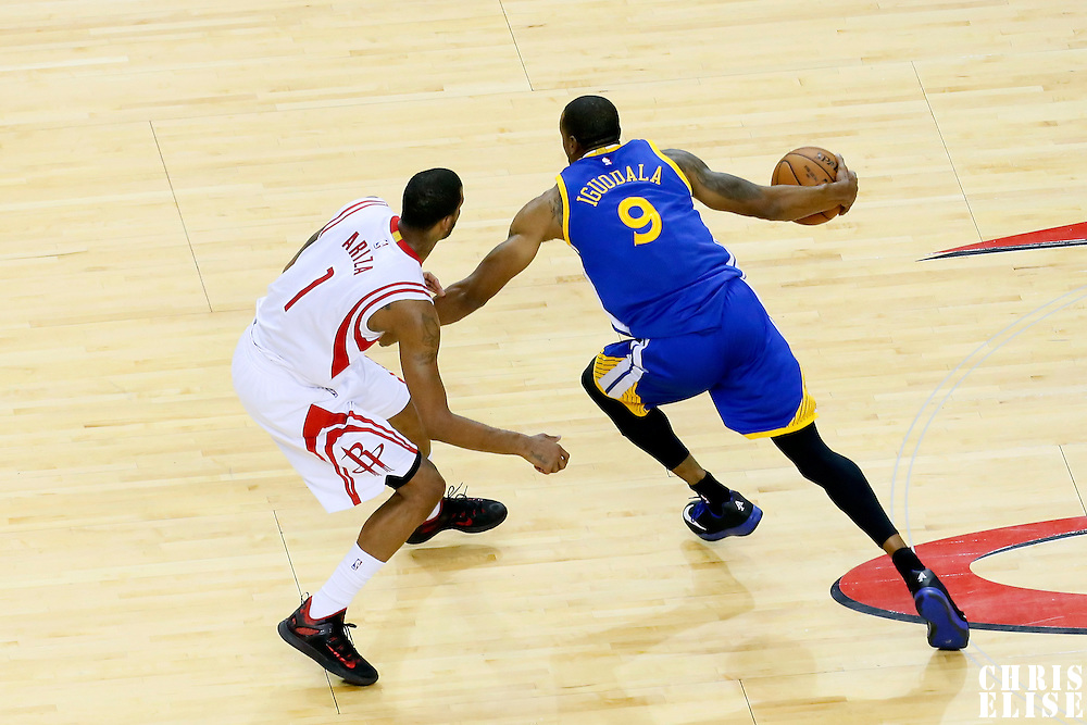 23 May 2015: Golden State Warriors guard Andre Iguodala (9) drives past Houston Rockets forward Trevor Ariza (1) during the Golden State Warriors 115-80 victory over the Houston Rockets, in game 3 of the Western Conference finals, at the Toyota Center, Houston, Texas, USA.