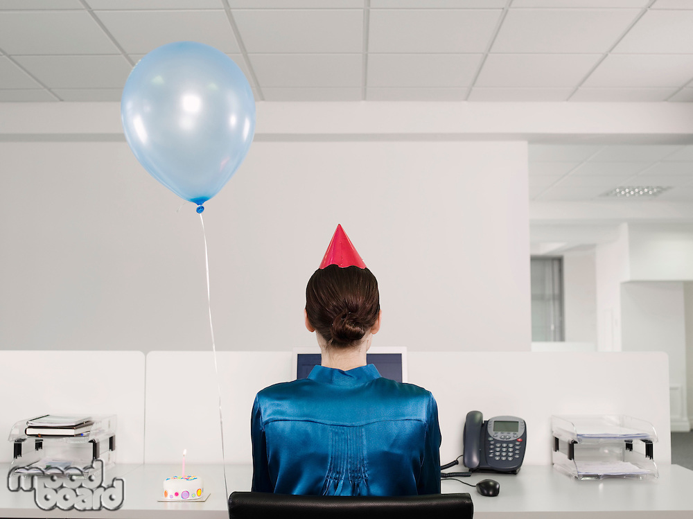 Woman celebrating birthday working alone in office