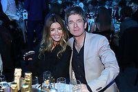 Noel Gallagher and Wife Sara MacDonald at their table enjoying drinks