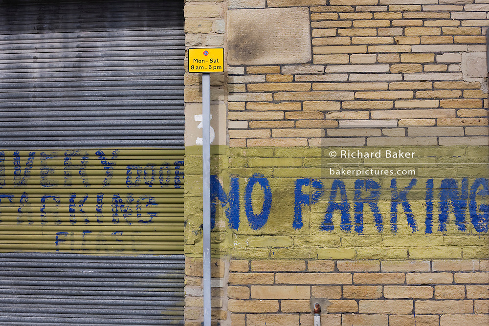 On brick and metal shutters, the words No Parking and Please have been painted by hand in blue against a background stripe of yellow on a wall in a quiet street near Bradford city centre, Yorkshire. A modern Monday to Saturday 8am to 6pm parking zone sign is also a vertical line that is central to the picture.