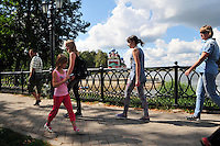 """Pedestrians ply the elegant riverside walkways along the Volga in Uglich, Russia. The colorful onion domes of the church of Saint Dimitry on the Blood, built in 1690, are in the background. As one of Russia's """"Golden Ring"""" cities, Uglich is designated a town of significant cultural importance."""
