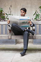Young Indian businessman reading newspaper while sitting on bench