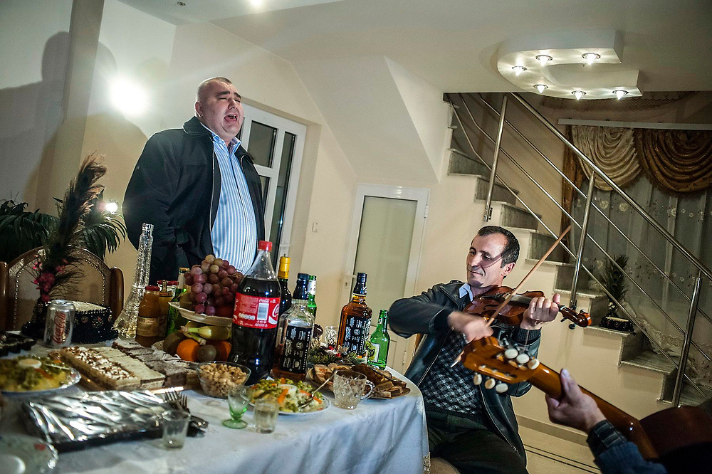 One of the most influential businessmen in Certeze village, sings a song at a celebration in the village. Two musicians accompany him on guitar and violin.