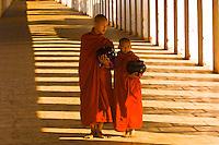 Two monks walking down hallway at the Shwezigon Pagoda, Bagan, Myanmar (Burma)