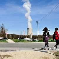 Girls strolling along a road close to G&ouml;sgen Nuclear Power Plant (Kernkraftwerk G&ouml;sgen), with a plume of smoke coming from its cooling tower. <br />
