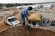 Building an earth platform for a water tank. Refugee camp. Kiran. Batticaloa district.