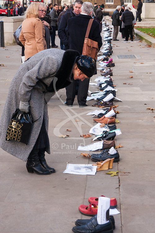 London, December 10th 2014. The shoes of hundreds of victims who died in Ireland, North and South during the Troubles are lined up opposite Downing Street as families demand that a proper investigation into over 3,600 deaths and 40,000 injuries on all sides, sets the truth free. PICTURED: A woman reads the message attached to a pair of wedges.