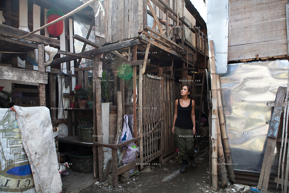 UK celebrity Myleene Klass walks through the narrow slum lane that leads to Vilma Tacuyo's one room home in an urban slum in Paranaque City, Metro Manila, The Philippines on 18 January 2013. Vilma had raised her first 3 children on formula and had to cut down on food for her family to afford it. Both John Ashley, 4, and Justin (sleeping), 3, are malnourished and stunted, and after losing one of her children, she now breastfeeds her youngest, Ulderico. Photo by Suzanne Lee for Save the Children UK