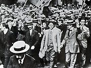 Frenchmen marching through Paris, enthusiastically waving flags and singing patriotic songs, after the declaration of war, August 1914.