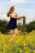 Editorial photo of fashion model Tayler Campbell in field of yellow flowers beside  barbed wire fence by fashion photographer Gerard Harrison.