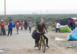 "© Licensed to London News Pictures. 30/08/2015. Calais, France. One of the British cyclists from ""Bikes Beyond Borders"" arrives to the refugee camp, also known as the Jungle, after riding from London to donate bicycles and supplies to support the life at the site. Photo credit : Isabel Infantes/LNP"