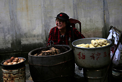 Chinese food seller Liu Fuxiu sells eggs, sweet potatoes and corn at her stall outside the 'Water Dripping Cave' compound, where Mao Zedong stayed briefly for 11 days in 1966 and is thought to have contemplated the start of the Cultural Revolution there in Shaoshan, Hunan Province in central China, 28 April 2016. Shaoshan is the hometown of former Communist leader Mao Zedong, popularly known as Chairman Mao. Thousands of visitors descend on this small Chinese town burrowed in the hills of Central China's Hunan province to pay homage to the great helmsman everyday. It is one of the core sites of the 'Red Tourism' industry, where communist party cadres and ordinary Chinese tourists alike seek to relive the experiences and rekindle the spirit of the revolutionaries.