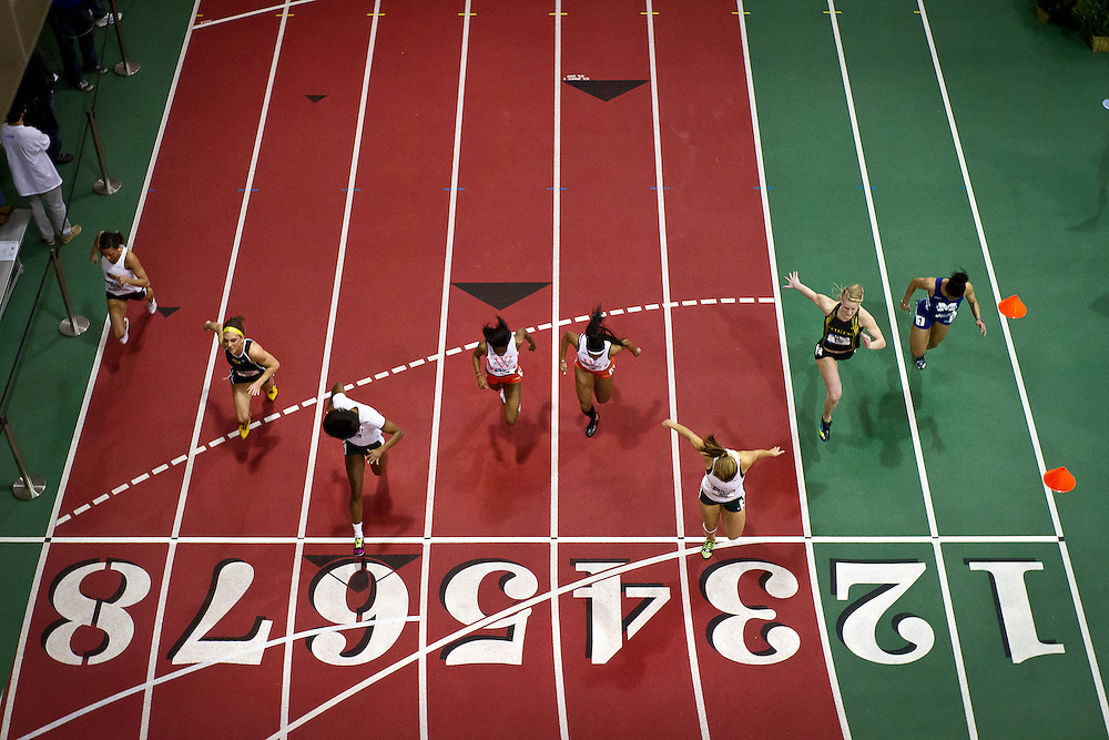 The field of runners in the first heat of the Women's 60m dash break across the finish line during preliminary competition on Friday at the NCAA Division III Indoor Track and Field National Championships at Grinnell College.