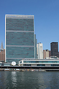 The headquarters of the United Nations, with the tall building of the Secretariat dominating the skyline, and the low horizontal Conference building facing FDR Drive and the East River. The Chrysler Building can be seen to the left of the Secretariat.