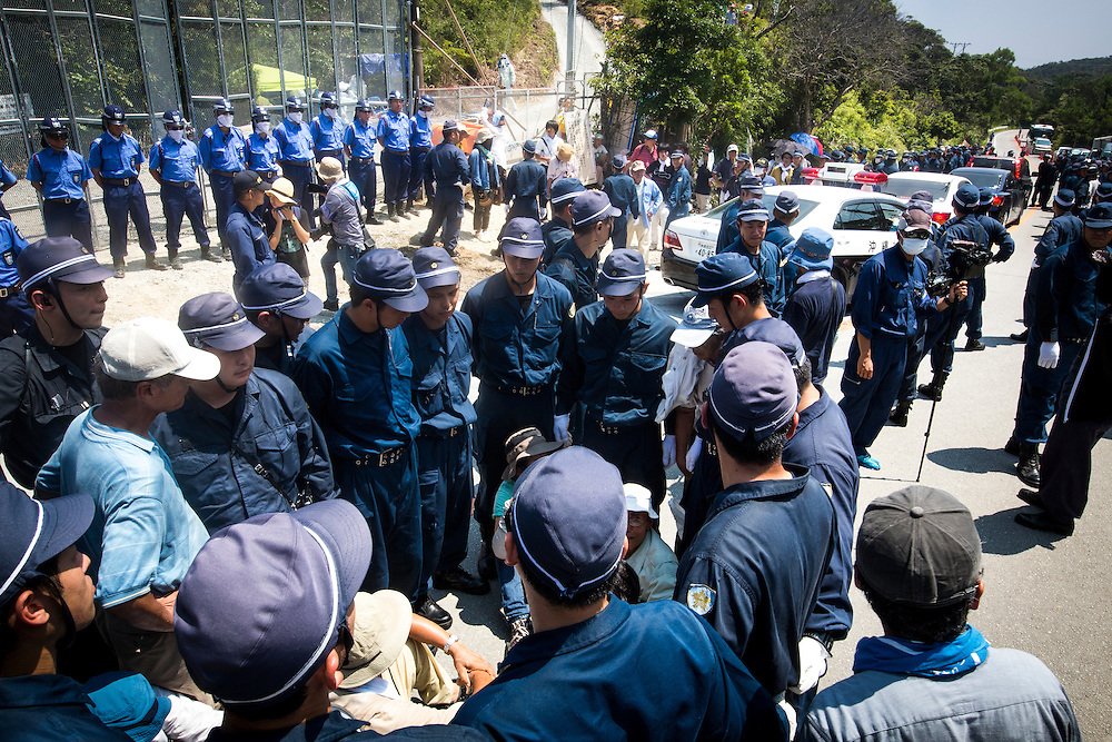OKINAWA, JAPAN - AUGUST 19 : Police guard the Anti U.S base protesters from staging a sit-in protest against the construction of helipads in front of the gate of U.S. military's Northern Training Area in the village of Higashi, Okinawa Prefecture, on August 19, 2016. Japanese government resume construction of total six helipads in a fragile ten million year old Yanbaru forest that is home to endemic endangered species such as the Okinawan rail and Okinawan wood pecker. (Photo by Richard Atrero de Guzman/NURPhoto)