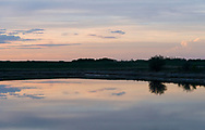 Soft pastel colors fill the spring prairie skies, reflected in still waters below