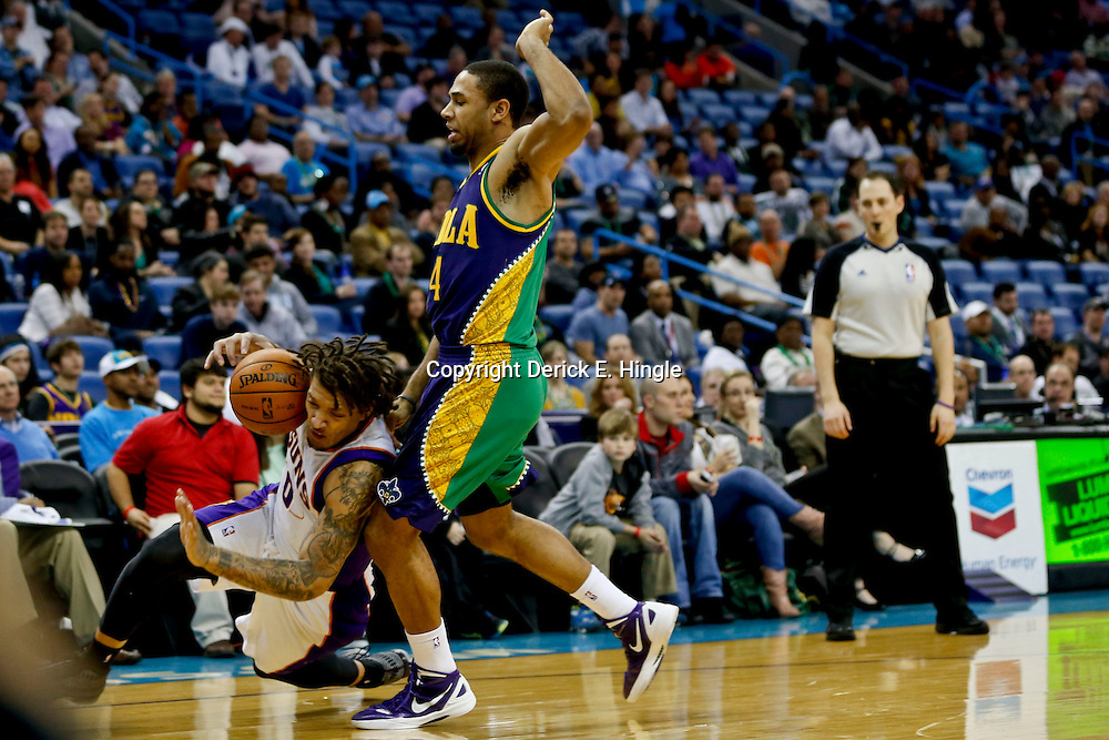 Feb 6, 2013; New Orleans, LA, USA; Phoenix Suns small forward Michael Beasley (0) slips as he attempts to drive past New Orleans Hornets shooting guard Xavier Henry (4) during the second half of a game at the New Orleans Arena. The Hornets defeated the Suns 93-84. Mandatory Credit: Derick E. Hingle-USA TODAY Sports