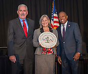 Lindsey Pollock, center, accepts an award for the Urban Harvest @ Garden Oaks Montessori from Daniel Sullenbarger, left, and Sylvester Turner, right, during the Keep Houston Beautiful Mayor's Proud Partner Awards luncheon at the Hilton Americas, November 7, 2016.