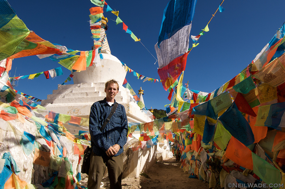 A tourist poses amoung Tibetan Buddhist prayer flags near Deqin, Tibet (China).
