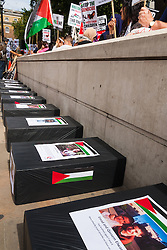 "London, August 23rd, 2014. ""Coffins"" line the pavement, each one bearing a picture of children killed since Israel began its Operation Protective Edge against Hamas as hundreds of pro- Palestine protesters demonstrate outside Downing Street demanding that Britain stops arming Israel."