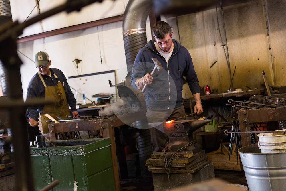 Blacksmiths working at a forge in an iron working shop in Charleston, SC