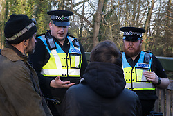 Denham, UK. 3 February, 2020. Police liaison officers speak to Mark Keir and Sarah Green of Save Colne Valley as environmental activists occupy a bridge in Denham Country Park so as to seek to prevent works for the HS2 high-speed rail link including the felling of 200 trees and the construction of a Bailey bridge, compounds, fencing and a parking area. Part of the location for the work lies within a wetland nature reserve forming part of a Site of Metropolitan Importance for Nature Conservation (SMI). In spite of a substantial police presence, HS2 were not able to proceed with the work for the day.