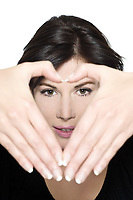 studio shot portrait on isolated white background of a Beautiful Woman gesturing heart shape with hands