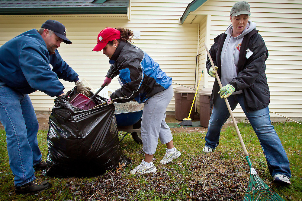 "JEROME A. POLLOS/Press..Bret Bloodgood and Belinda Schrankel load a pile of leaves into a bag as Jodie Lynch rakes together another pile Wednesday during the ""Rake and Run"" volunteer event put on by CareNet, an organization made up of North Idaho senior service providers. Five teams tended to the yards of 13 senior citizens in Coeur d'Alene, Post Falls and Rathdrum helping clear debris, rake leaves, pull weeds and mow lawns."