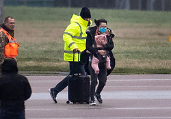 © Licensed to London News Pictures. 09/02/2020. Brize Norton, UK. A passenger disembarks from a charter flight carrying a baby as she is evacuated from Wuhan, China to RAF Brize Norton in Oxfordshire. Fears of the spread of the corona virus have lead to this third charter flight being organised to bring 200 people to the UK. The passengers will be quarantined at a facility in Milton Keynes for 14 days. Photo credit: Peter Macdiarmid/LNP