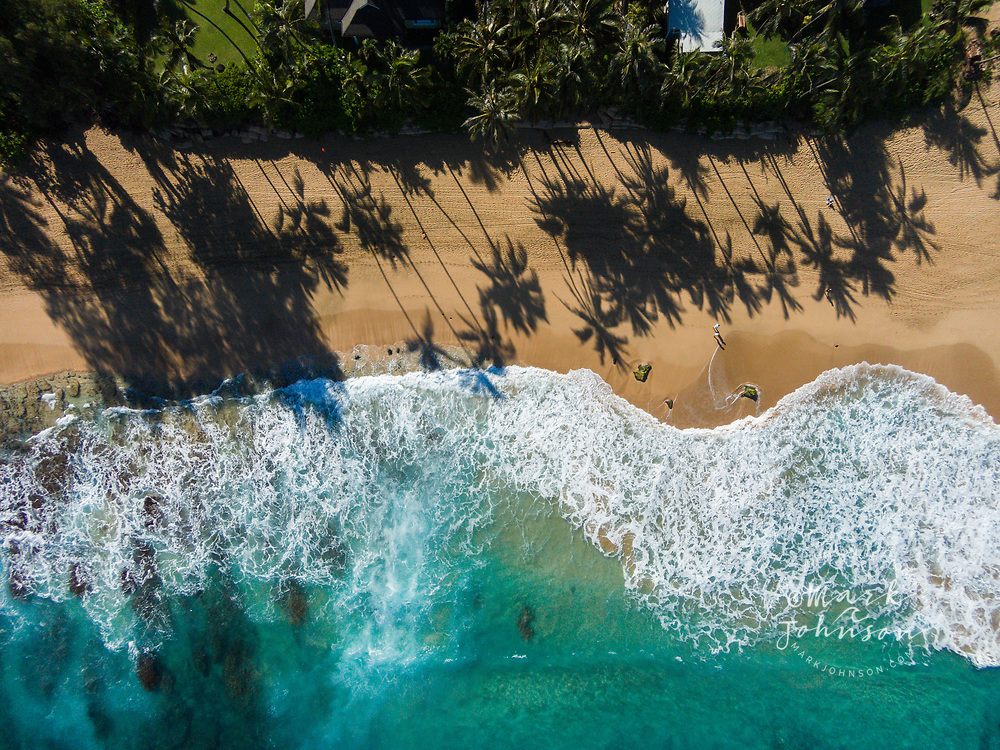 Aerial photo looking straight down at Haena Beach with people walking and long palm tree shadows, Kauai, Hawaii