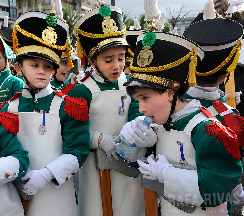 A boy tries to open a bottle of water as he takes part in San Sebastian's Tamborrada. Some thousands soldiers-clad children march and play drums, on January 20, 2010, during a parade to celebrate San Sebastian's day, the northern Spanish Basque city of San Sebastian's main feast. PHOTO / RAFA RIVAS