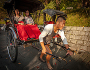 Rickshaw driver sets off with two women to tour Kyoto, Japan.