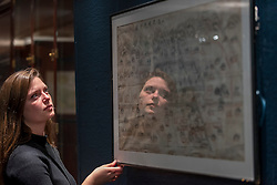 "© Licensed to London News Pictures. 03/11/2016. London, UK. A staff member inspects a rare map of ancient China at the preview of Chinese artworks entitled ""Treasures Of The Song & Qing Dynasties"" to be auctioned at Sotheby's in November.   Photo credit : Stephen Chung/LNP"