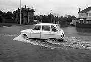 "Flooding at the Dodder..1986..26.08.1986..08.26.1986..28th August 1986..As a result of Hurricane Charly (Charlie) heavy overnight rainfall was the cause of severe flooding in the Donnybrook/Ballsbridge areas of Dublin. In a period of just 12 hours it was stated that 8 inches of rain had fallen. The Dodder,long regarded as a ""Flashy"" river, burst its banks and caused great hardship to families in the 300 or so homes which were flooded. Council workers and the Fire Brigades did their best to try and alleviate some of the problems by removing debris and pumping out some of the homes affected..Note: ""Flashy"" is a term given to a river which is prone to flooding as a result of heavy or sustained rainfall...Photograph of motorists trying to avoid the worst of the flooding by driving on the 'wrong' side of the road on the Lr. Dodder Road, Rathfarnham.. Motorists were advised to be vigilant as manhole covers had been displaced by the water pressure and were lying unseen underwater."