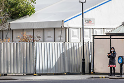 © Licensed to London News Pictures. 18/03/2020. London, UK. A women in a medical mask walks past a makeshift mortuary which has been put up behind Westminster Coroners Court in Horseferry Road as the Coronavirus pandemic crisis continues. Photo credit: Alex Lentati/LNP