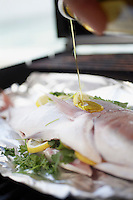 Pouring oil over Fish on Grill