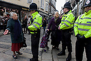 Two elderly ladies reason with police about a local matter during a protest in the centre of Canterbury, Kent England.