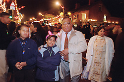 Family group standing together in street celebrating Diwali; festival of light,