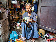 08 APRIL 2016 - BANGKOK, THAILAND: A woman counts her cash before going out to go shopping at a market near Mahakan Fort. The community is known for fireworks, fighting cocks and bird cages. Mahakan Fort was built in 1783 during the reign of Siamese King Rama I. It was one of 14 fortresses designed to protect Bangkok from foreign invaders, and only of two remaining, the others have been torn down. A community developed in the fort when people started building houses and moving into it during the reign of King Rama V (1868-1910). The land was expropriated by Bangkok city government in 1992, but the people living in the fort refused to move. In 2004 courts ruled against the residents and said the city could take the land. The final eviction notices were posted last week and the residents given until April 30 to move out. After that their homes, some of which are nearly 200 years old, will be destroyed.     PHOTO BY JACK KURTZ