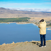 Man taking photograph from summit of Mt John, Tekapo
