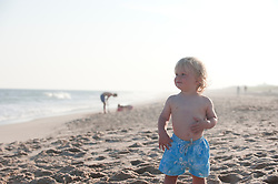 child standing alone at the beach in East Hampton, NY