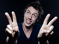 studio portrait on black background of a funny expressive caucasian man victory sign triumph