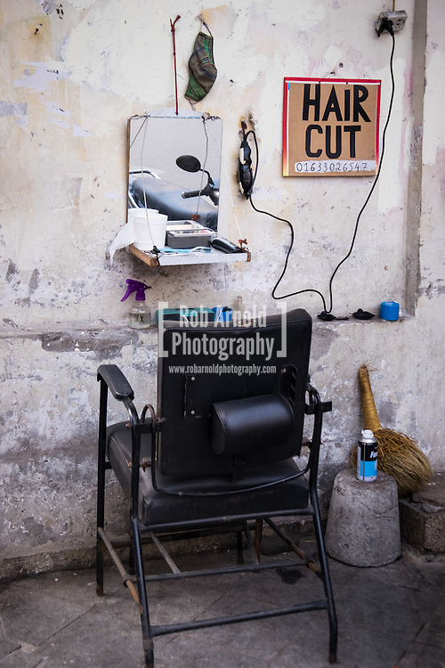A street barbers offering cheap hair cuts in Hanoi's Old Quarter.