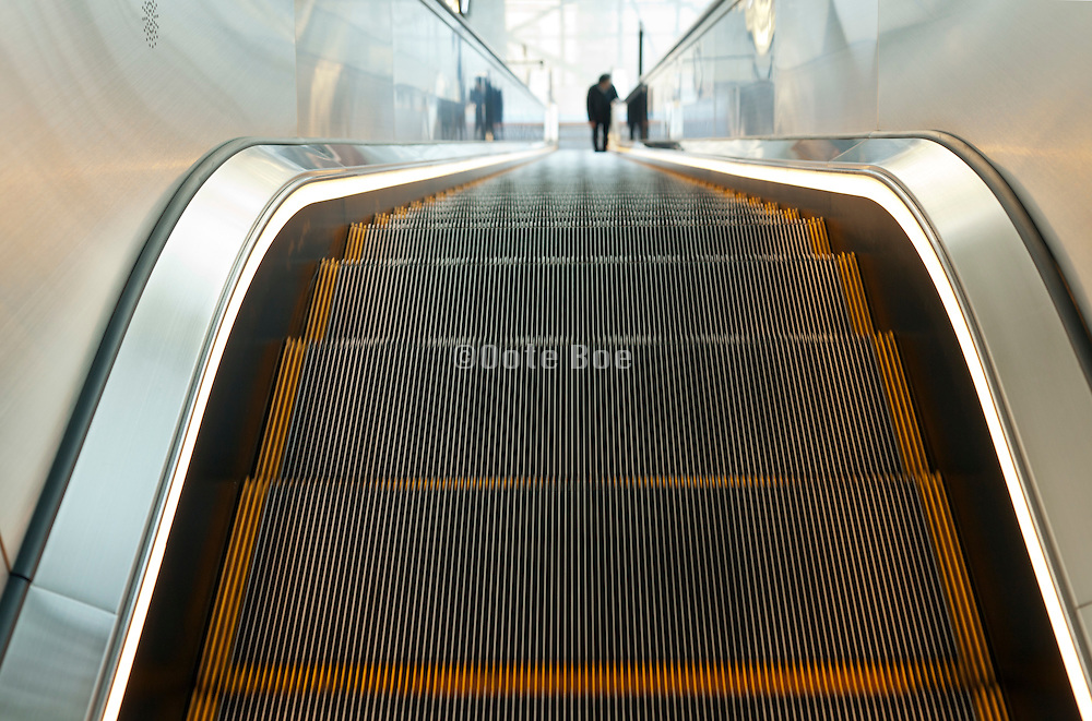 person riding a long escalator
