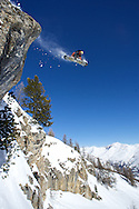 Male Snowboarder jumps frm rock on mountainside, Serre Chevalier, France