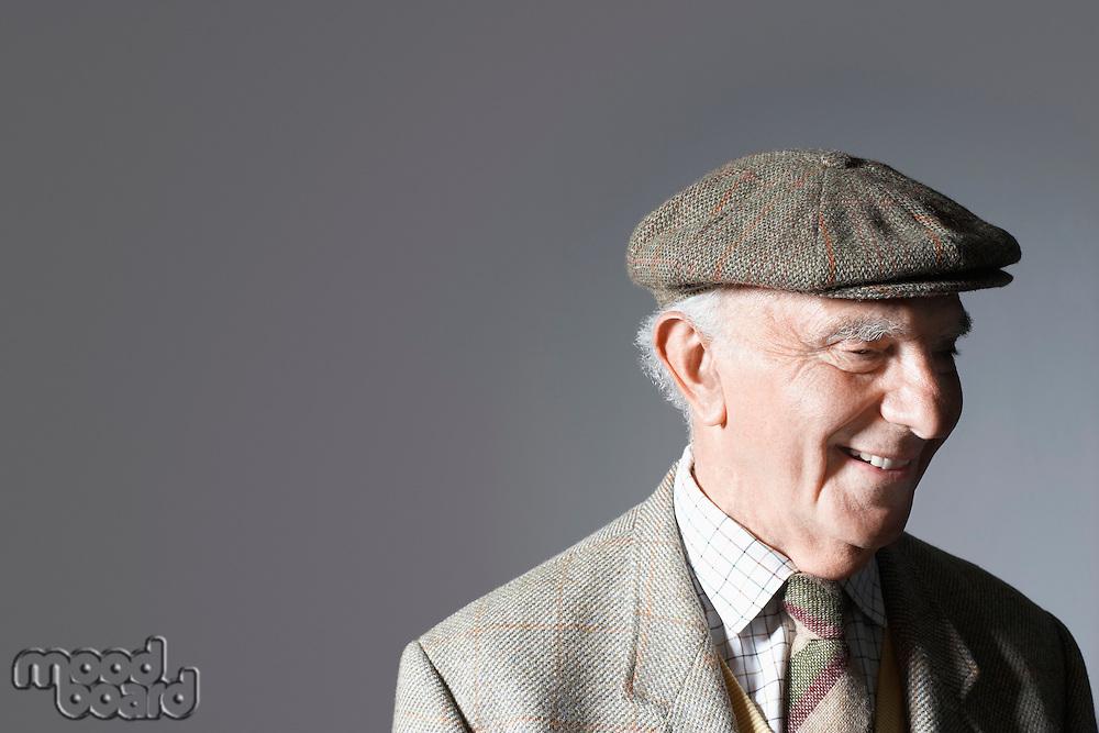 Senior man in flat cap head and shoulders in studio