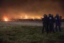 """Dschungel von Calais: Das wilde Fl¸chtlingslager wird ger‰umt und die Fl¸chtlinge in Aufnahmezentren verteilt / 241016 *** Calais, Pas-de-Calais, France - 24.10.2016    <br />  <br /> Clashes between a small group of camp residents and the police. Start of the eviction on the so called îJungle"""" refugee camp on the outskirts of the French city of Calais. Refugees and migrants leaving the camp to get with buses to asylum facilities in the entire country. Many thousands of migrants and refugees are waiting in some cases for years in the port city in the hope of being able to cross the English Channel to Britain. French authorities announced a week ago that they will evict the camp where currently up to up to 10,000 people live.<br /> <br /> <br /> Ausschreitungen zwischen einer kleinen Gruppe von Camp-Bewohnern und der Polizei. Beginn der Raeumung des so genannte îJungleî-Fluechtlingscamp in der franzˆsischen Hafenstadt Calais. Fluechtlinge und Migranten verlassen das Camp um mit Bussen zu unterschiedlichen Asyleinrichtungen gebracht zu werden. Viele tausend Migranten und Fluechtlinge harren teilweise seit Jahren in der Hafenstadt aus in der Hoffnung den Aermelkanal nach Groflbritannien ueberqueren zu koennen. Die franzoesischen Behoerden kuendigten vor einigen Wochen an, dass sie das Camp, indem derzeit bis zu bis zu 10.000 Menschen leben raeumen werden. <br /> <br /> Photo: Bjoern Kietzmann"""