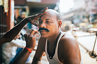 A man gets his mustache dyed and waxed on a street corner in old Kolkata.